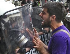 Manifestante enfrenta a polícia nas ruas de Atenas, na tentativa de pressionar o governo contra o pacote de austeridade imposto pelo Fundo Monetário Internacional (FMI) e pela UE