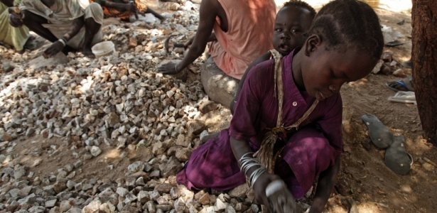 Com a irmã presa às costas, menina quebra pedras em Juba (Sudão)