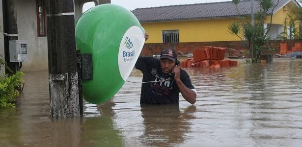Homem tenta usar telefone público em rua completamente alagada de Criciúma