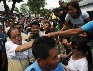 O candidato presidencial Benigno Aquino III é saudado por simpatizantes e correligionários durante chegada à zona eleitoral em Hacienda Luisita, província de Tarlac, no norte das Filipinas