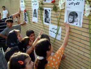 Crianças iranianas observam fotos das irmãs siamesas mortas numa cirurgia em Teerã