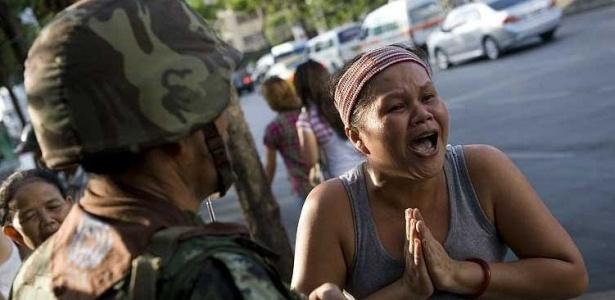 Mulher grita diante de soldado na região de acampamento fortificado de manifestantes em Bancoc