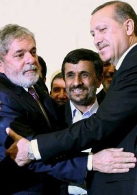 O presidente Luiz Inácio Lula da Silva, o presidente iraniano, Mahmoud Ahmadinejad (centro), e o primeiro-ministro turco, Recep Tayyip Erdogan, se abraçam durante cerimônia de assinatura de acordo nuclear entre os 3 países