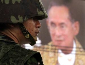 Militar patrulha Bancoc diante de uma foto do rei Bhumibol Adulyadej