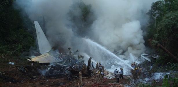 Bombeiros combatem as chamas de um avião que explodiu após sair da pista na Índia