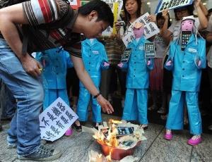 Manifestantes chineses queimam produtos eletrônicos durante ato contra uma série de suicídios ocorridos entre funcionários da empresa Foxconn