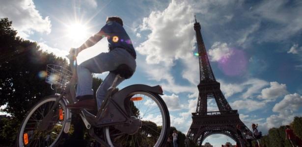 Turista circula por rua em Paris (França), onde se utiliza o sistema Vélib de aluguel de bicicletas