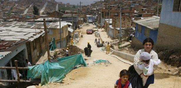 Mulher caminha com seus filhos em favela de Ciudad Bolívar, ao sul da capital colombiana Bogotá