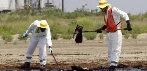 Trabalhadores tentam remover o óleo na praia de Grand Terre, na Louisiana; <b>VEJA MAIS</b>