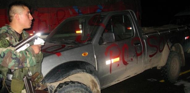 Soldado perto de um carro pichado pelo grupo guerrilheiro Sendero Luminoso, no Peru