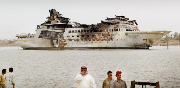 Iraquianos observam iate do ex-ditador do país, Saddam Hussein, destruído em bombardeio da coalizão anglo-americana no rio Shatt al Arab, em Basra
