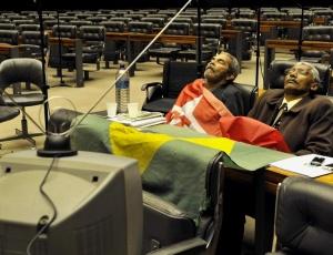 O deputado Domingos Dutra (PT-MA), à direita, em greve de fome contra aliança do partido no Estado, e o líder camponês Manoel Conceição dormem diante da TV