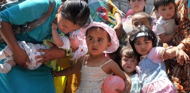 Mulher e crianças uzbeques cruzam cerca de separação na fronteira entre Quirguistão e o Uzbequistão