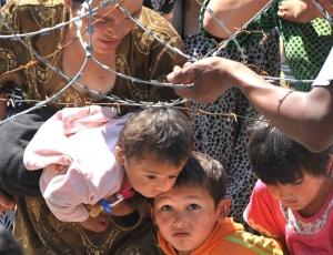 Crianças quirguizes ultrapassam cerca de arame