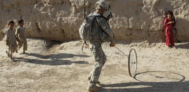 Soldado norte-americano e crianças afegãs brincam com uma roda de bicicleta velha durante uma patrulha na localidade de Maruf-Kariz, no distrito de Dand, ao sul de Kandahar