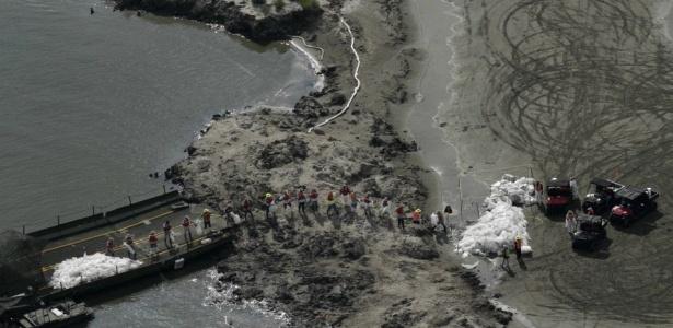 Trabalhadores contratados pela BP transportam sacos de areia para uma barca durante os esforços de limpeza