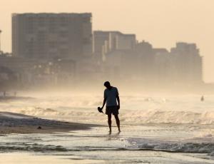 Homem caminha por praia atingida pela mancha de óleo ocasionado por vazamento após explosão de plataforma no golfo do México