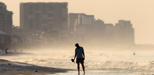 Homem caminha por praia atingida pela mancha de óleo ocasionada por vazamento após explosão de plataforma no golfo do México