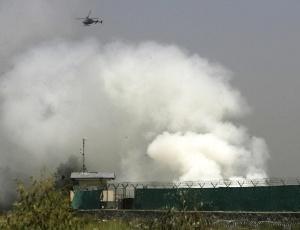 Helicóptero da Otan sobrevoa nuvem de fumaça em aeroporto em Jalalabad, que foi atacado por forças talebans; <b>VEJA MAIS FOTOS DO DIA</b>