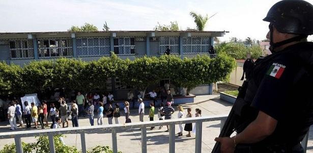 Vigiados pela polícia, eleitores aguardam na fila para votar na cidade do México