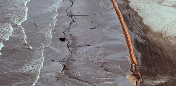 Barreiras de contenção tentam absorver o óleo que chega à praia na Ilha de Elmer, na Louisiana, após explosão da plataforma da BP no golfo do México; veja mais fotos dos esforços de limpeza