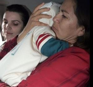 Mãe de Eliza Samudio carrega o neto após conseguir a guarda da criança