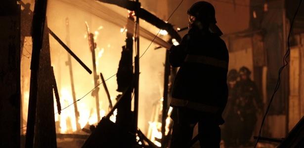 Bombeiro tenta conter incêndio que destruiu favela na zona leste de São Paulo