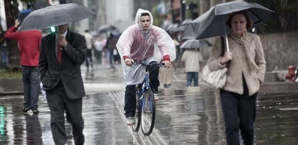 Pedestres e ciclista percorrem a avenida Paulista, em São Paulo, em dia chuvoso