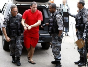 Luiz Henrique Ferreira Romão, o Macarrão (de vermelho), chega à delegacia de Belo Horizonte (MG) para prestar depoimento