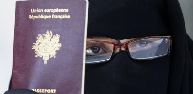 Imigrantes na europa: mulher muçulmana vestindo o niqab mostra passaporte francês
