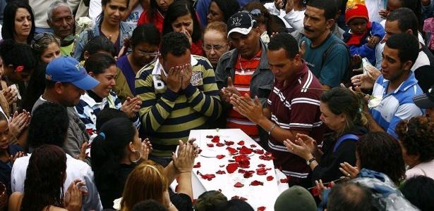 O pai de Wesley (no centro) chora com as mãos no rosto durante o enterro do filho - André Teixeira / Agência O Globo