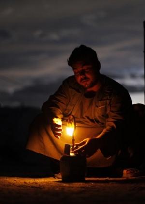 Refugiado afegão acende uma lâmpada a gás, do lado de fora de sua tenda. Representantes de 60 países se reúnem nesta terça-feira em Cabul para discutir o futuro do país, envolvido em corrupção, guerra e extremismo