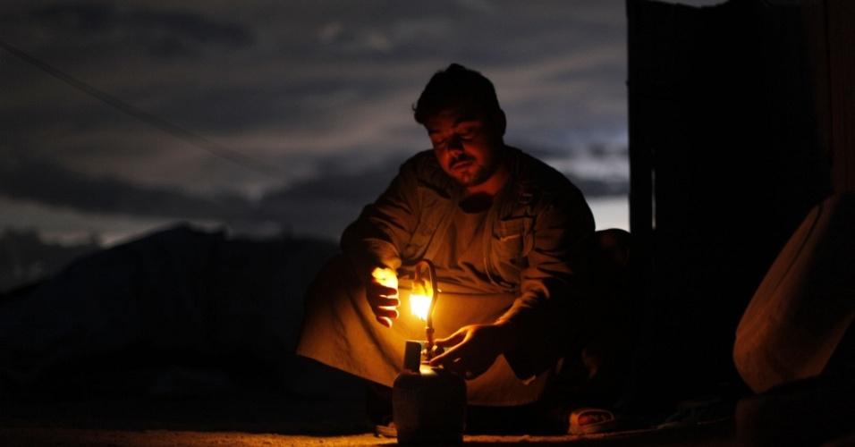 Refugiado afegão acende uma lâmpada a gás, do lado de fora de sua tenda. O Afeganistão é o país com o menor gasto de energia por pessoa no mundo