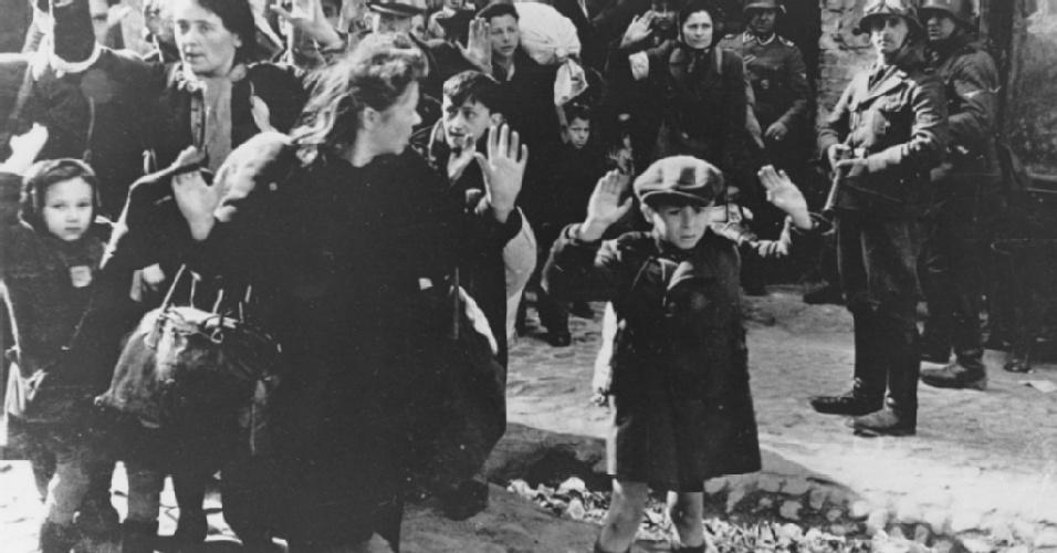 Gesto célebre do menino ameaçado pelos soldados alemães no gueto de Varsóvia em 1943, durante a Segunda Guerra Mundial