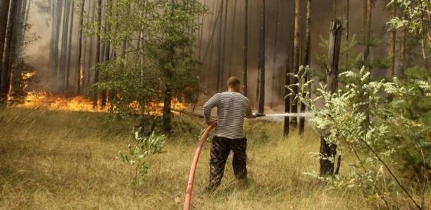Bombeiro voluntário tenta extinguir o fogo em uma floresta nos arredores de Voronezh (Rússia)