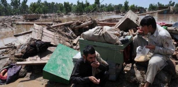 Sobreviventes comem arroz em frente de sua casa destruída em Nowshera; veja mais fotos