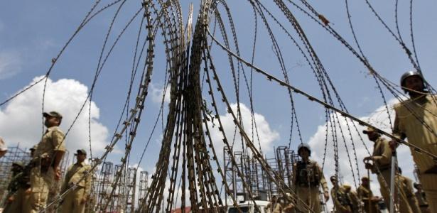 Policial indiano próximo a barricada feita para parar protestos na região de Srinagar, na Caxemira