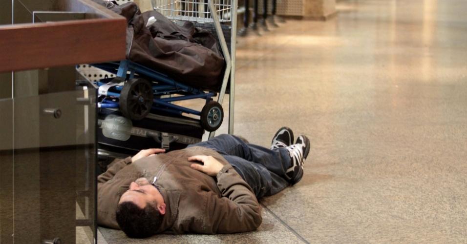 Homem dorme à espera de voo no aeroporto de Guarulhos no começo da madrugada