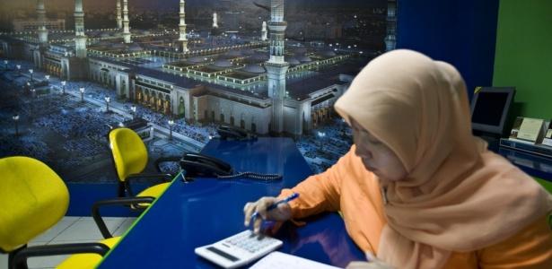 Membro da equipe de uma agência de viagens especializada em pacotes islâmicos em Jacarta, na Indonésia