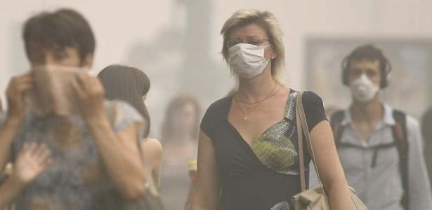 Pedestres utilizam máscaras para cobrir rosto da fumaça nas ruas de Moscou