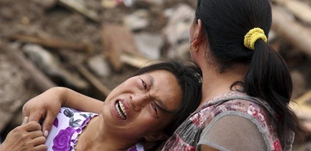 Mulher chora pelos membros de sua família que estão desaparecidos em deslizamento de terra que ocorreram após as fortes chuvas na província de Gansu, na China