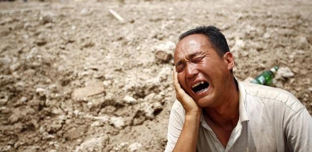 Homem lamenta a tragédia; mais de mil pessoas estão desaparecidas; <b>VEJA MAIS FOTOS</b>