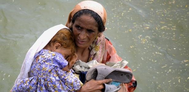 Mulher desabrigada pelas inundações carrega criança em Muzaffargarh, na região central do Paquistão