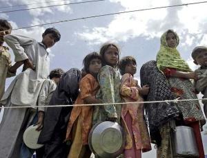 Sobreviventes das enchentes no Paquistão fazem fila para receber alimento. Grupo taleban quer impor ajuda ao país