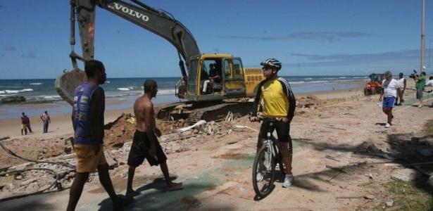 Escavadeira limpa os restos das barracas demolidas na praia de Patamares, em Salvador