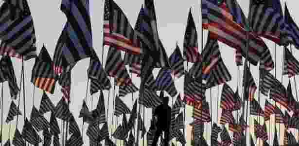 Homem caminha entre cerca de 3000 mil bandeiras posicionadas por estudantes e membros da Universidade Pepperdine, em Malibu, nos Estados Unidos, em memória das vítimas do atentado ocorrido em 11 de setembro de 2001, em Nova York -  Mark Ralston/AFP