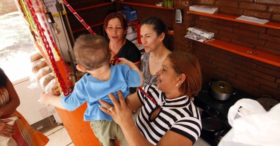 Sonia de Fatima Moura (centro) observa Roseli Palmeiira (direita) e Wennya Pereira Souza (esquerda) brincarem com seu neto Bruno Samudio, em barraca de doces, no distrito Aiandui, Mato Grosso do Sul