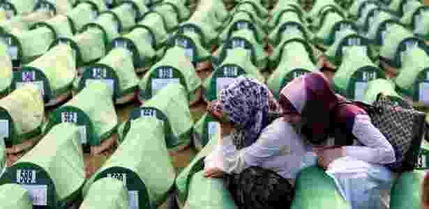 Muçulmanas choram entre urnas fúnebres durante o enterro de 775 vítimas do massacre de Srebrenica recentemente identificadas - Fehim Demir/EFE