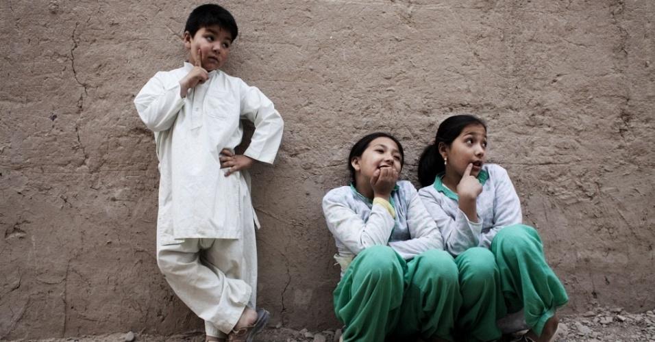 Mehran Rafaat (à esq) ao lado de suas irmãs Benafsha e Behishta na frente da casa da família em Qala-e-Naw