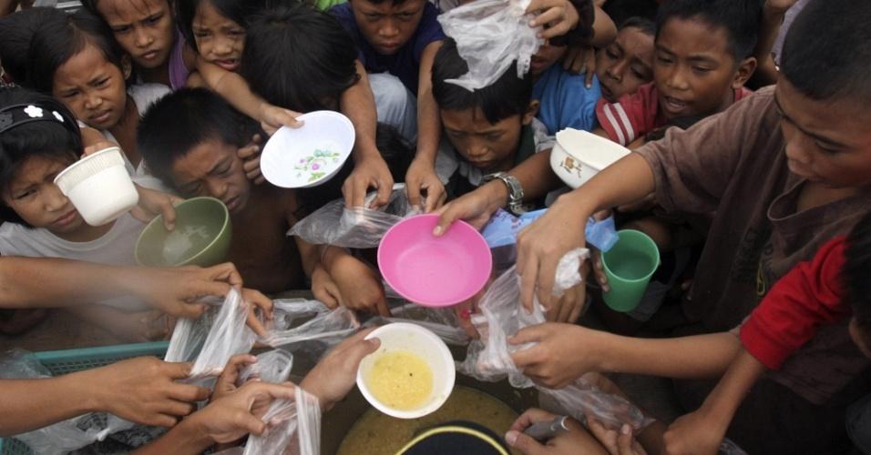 Crianças carregam tigelas e se empurram para conseguir uma refeição gratuita na pobre área de Baseco, nas Filipinas. O presidente do país, Benigno Aquino III, diz que apenas o controle da taxa de natalidade pode resolver a questão da pobreza